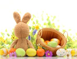 Fluffy Easter bunny with a basket full with painted eggs